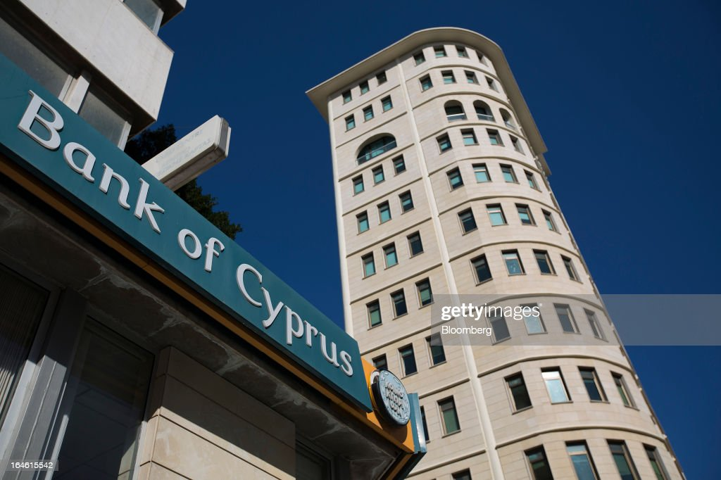 A sign hangs above a Bank of Cyprus Plc branch in Nicosia, Cyprus, on Monday, March 25, 2013. Cyprus dodged a disorderly default and unprecedented exit from the euro by bowing to demands from creditors to shrink its banking system in exchange for 10 billion euros ($13 billion) of aid. Photographer: Simon Dawson/Bloomberg via Getty Images