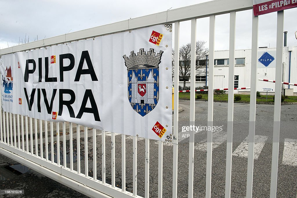A sign hangs on the entrance gate at the Pilpa ice cream factory in Carcassonne, southern France, as workers take part in surveillance rounds to stop the new factory owner from taking or dismantling factory equipment and machines, on December 27, 2012. 112 workers face the threat of being layed-off since July 2012 when the factory's owner sold the site to the R&R ice cream company and have struggled to keep the site and its jobs ever since. As the workers await court rulings pertaining to the factory site and its future, workers say they are being vigilant and have instituted rounds and a night guard to make sure R&R does not leave with the machines and equipment, thereby making it impossible for workers to consider continuing production at the site.