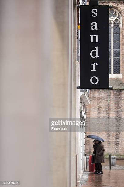 A sign hangs outside a Sandro luxury clothing store operated by SMCP Group as pedestrians shelter under umbrellas in Toulouse France on Wednesday Feb...