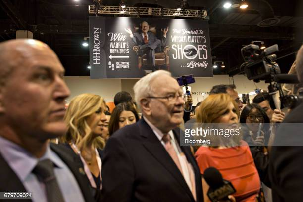A sign hangs overhead as Warren Buffett chairman and chief executive officer of Berkshire Hathaway Inc center tours the exhibit floor ahead of the...