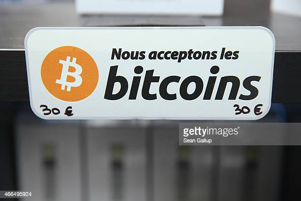 A sign in French that reads 'We accept bitcoins' hangs at a display of the LedgerWallet Nano USB stick that enables securityprotected transactions...