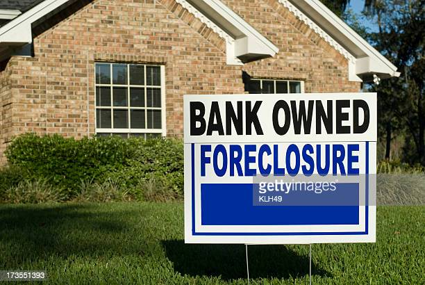 A sign in the yard of a house that says foreclosure