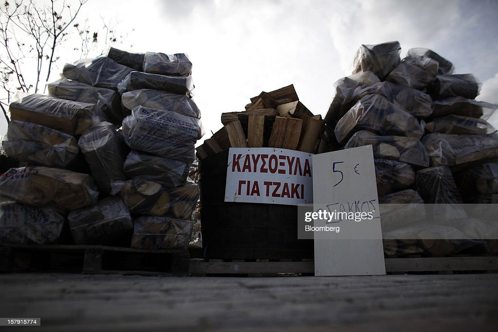 A sign indicates the price of firewood beside bags of cut logs at a wood store in Athens, Greece, on Friday, Dec. 7, 2012. Greece, the epicenter of Europe's debt crisis since revealing a bloated spending gap in late 2009, has faced regular demands to get a firmer grip on the budget or risk being forced out of the euro. Photographer: Kostas Tsironis/Bloomberg via Getty Images