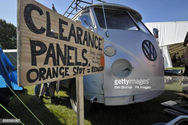 A sign indicating reduced next to a VW Splitscreen Type 2 Transporter in the trade stands area at Vanfest festival in the Three Counties Showground...