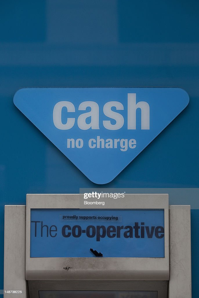 A sign is displayed above an automated teller machine (ATM) outside a Co-Operative Bank Plc branch in London, U.K., on Thursday, July 19, 2012. Lloyds Banking Group Plc agreed to sell 632 branches to Co-Operative Bank Plc for an initial 350 million pounds ($548 million), as the U.K.'s biggest mortgage lender divests assets to comply with its government bailout. Photographer: Simon Dawson/Bloomberg via Getty Images