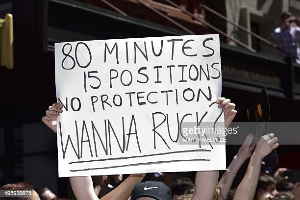 A sign is held up as New Zealand's All Blacks rugby team players take part in a parade by the team through the central business district of...