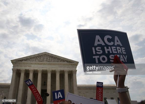 A sign is held up that reads 'ACA Is Here To Stay' front of the US Supreme Court after ruling was announced in favor of the Affordable Care Act June...