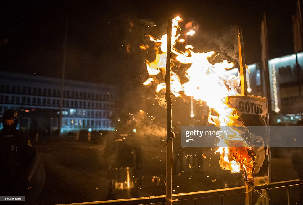 A sign is lit on fire in front of riot police during a demonstration against political corruption and the Prime Minister in Ljubljana, on January 11, 2013. Several thousand people in Slovenia's capital today joined in one of the biggest anti-government rallies in recent months, demanding the resignation of Prime Minister Janez Jansa, who has been accused of corruption. State radio estimated over 10,000 people took part in the protest called by civil groups under the slogan 'For the government's resignation and the renewal of Slovenia.' Police put the figure closer to 8,000. AFP PHOTO / Jure Makovec