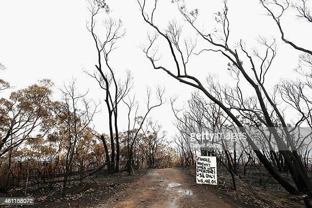A sign is posted in a driveway surrounded by scortched trees after a bushfire moved through Humbug Scrub in the Adelaide Hills on January 8 2015 in...