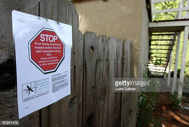 A sign is posted on a fence after Contra Costa County Mosquito and Vector Control District technician Josefa Cabada treated a neglected pool at a...