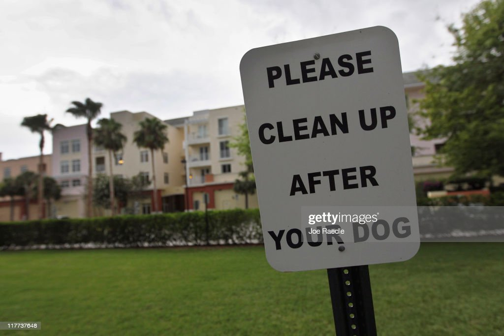 A sign is posted reading, ' Please clean up after your dog'' in The Village of Abacoa condominium complex where the condo association will begin testing dog feces to match its DNA to the dogs whose owners who are not picking up after their pets on June 30, 2011 in Jupiter, Florida. Beginning August 1, 2011 dog owners who live in the condos must pay a $200 one-time fee for a DNA swab to be taken from their dog's mouth to be held on file. If a dog's feces are found, a sample is sent to the DNA Pet World Registry to determine the dog's DNA and they match that with the one on file to determine who the owner is and than a fine will be issued for not picking up after their pet.