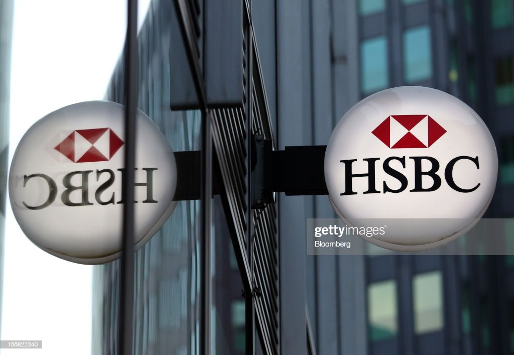 A sign is reflected as it hangs outside a HSBC Holdings Plc bank branch in London, U.K., on Thursday, Nov. 22, 2012. Shares of HSBC have climbed 26 percent this year in London trading, and 30 percent in Hong Kong, as Chief Executive Officer Stuart Gulliver pared costs and sold assets to revive profit and focus on emerging economies in which the bank has a greater market share. Photographer: Chris Ratcliffe/Bloomberg via Getty Images