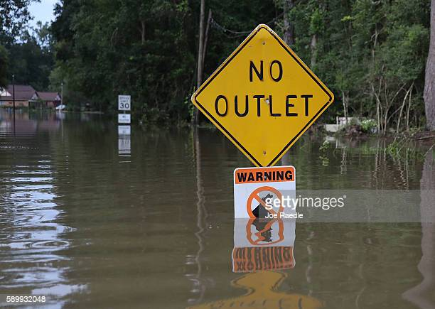 A sign is seen along a flooded road on August 15 2016 in Baton Rouge Louisiana Recordbreaking rains pelted Louisiana over the weekend leaving the...