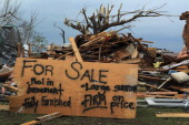 A sign is seen in front of a destroyed house indicating that it is for sale and that it includes a large sunroom after the home was destroyed when a...