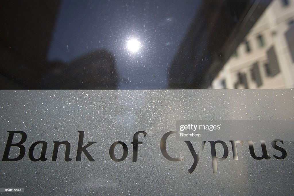 A sign is seen on the window of a door at a closed Bank of Cyprus Plc branch in Nicosia, Cyprus, on Monday, March 25, 2013. Cyprus dodged a disorderly default and unprecedented exit from the euro by bowing to demands from creditors to shrink its banking system in exchange for 10 billion euros ($13 billion) of aid. Photographer: Simon Dawson/Bloomberg via Getty Images