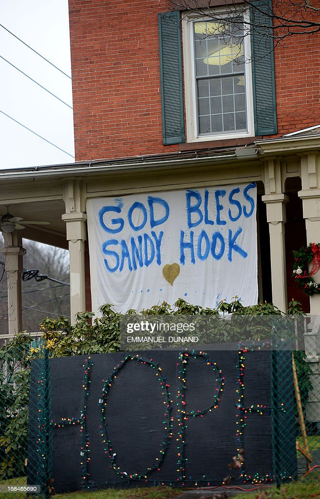 A sign is set up in memory of the victims of the December 14, 2012 elementary school shooting in Newtown, Connecticut on December 17, 2012. Funerals began Monday in the little Connecticut town of Newtown after the school massacre that took the lives of 20 small children and six staff, triggering new momentum for a change to America's gun culture. The first burials, held under raw, wet skies, were for two six-year-old boys who were among those shot in Sandy Hook Elementary School. On Tuesday, the first of the girls, also aged six, was due to be laid to rest. There were no Monday classes at all across Newtown, and the blood-soaked elementary school was to remain a closed crime scene indefinitely, authorities said. AFP PHOTO/Emmanuel DUNAND