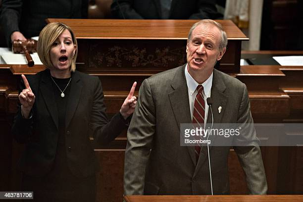 A sign language interpreter left works next Bruce Rauner governor of Illinois as he delivers a budget address in the House Chamber of the State...