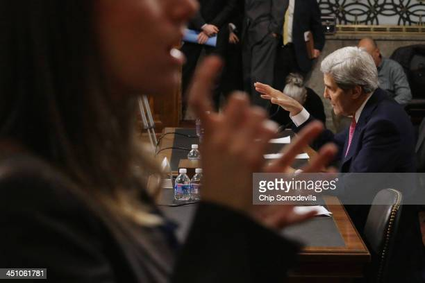 A sign language interpreter signs for the hearing impared as US Secretary of State John Kerry testifies before the Senate Foreign Relations Committee...