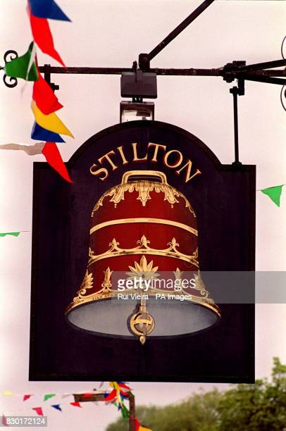 A sign marking Stilton with an illustration of a large bell during a traditional May Day 'Stilton cheeserolling' event at Stilton Cambridgeshire