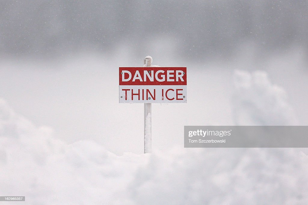 A sign marks the spot beyond which lies thin ice during outdoor shinny hockey action at the 4th Annual Lake Louise Pond Hockey Classic on the frozen surface of Lake Louise on March 2, 2013 in Lake Louise, Alberta, Canada.