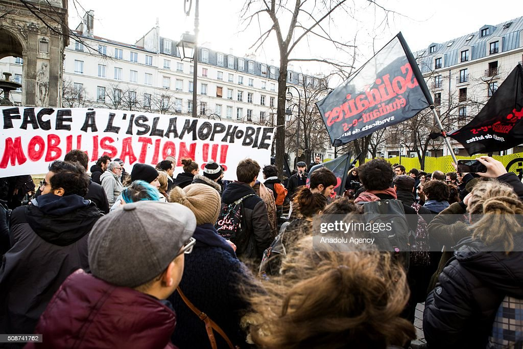A sign 'Mobilization Against Islamophobia' is seen in the background. Demonstrators holding flags gathered in Fontaine des innocents. Demonstration against extreme right and Islamophobia and all forms of racism (antifascist mobilization) in Paris, on February 06, 2016.