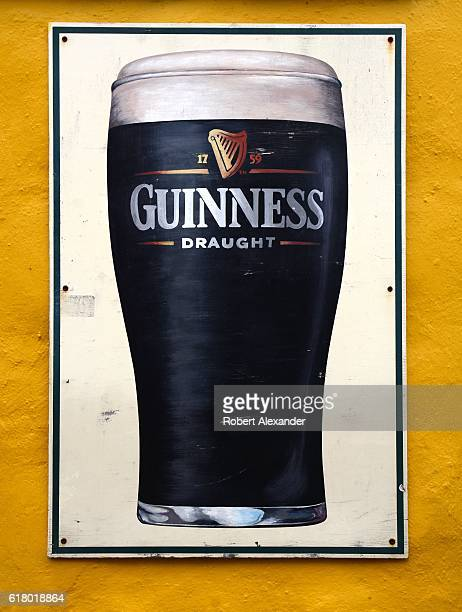 A sign mounted to the wall of an Dublin Ireland pub advertises Guinness draught Guinness stout is brewed in Dublin