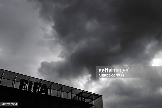 A sign of the FIFA is seen under eavy clouds on May 30 2015 at the top of World football governing body's headquarters in Zurich FIFA president Sepp...
