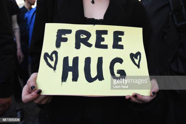 A sign offering a 'free hug' is held by a member of the public gathered at a candlelit vigil to honour the victims of Monday evening's terror attack...