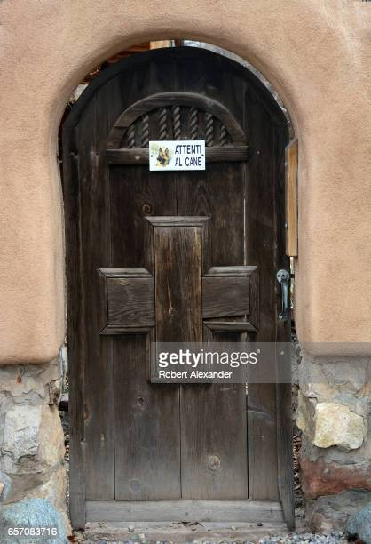 A sign on a residential yard entryway door in Santa Fe New Mexico advises visitors in Italian to 'Attenti al cane' or 'Beware of the dog'