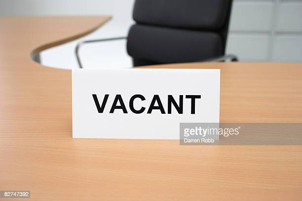 A VACANT sign on an empty office desk