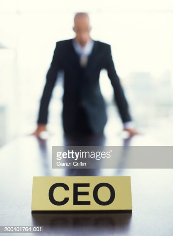 CEO sign on desk, close up, man in background