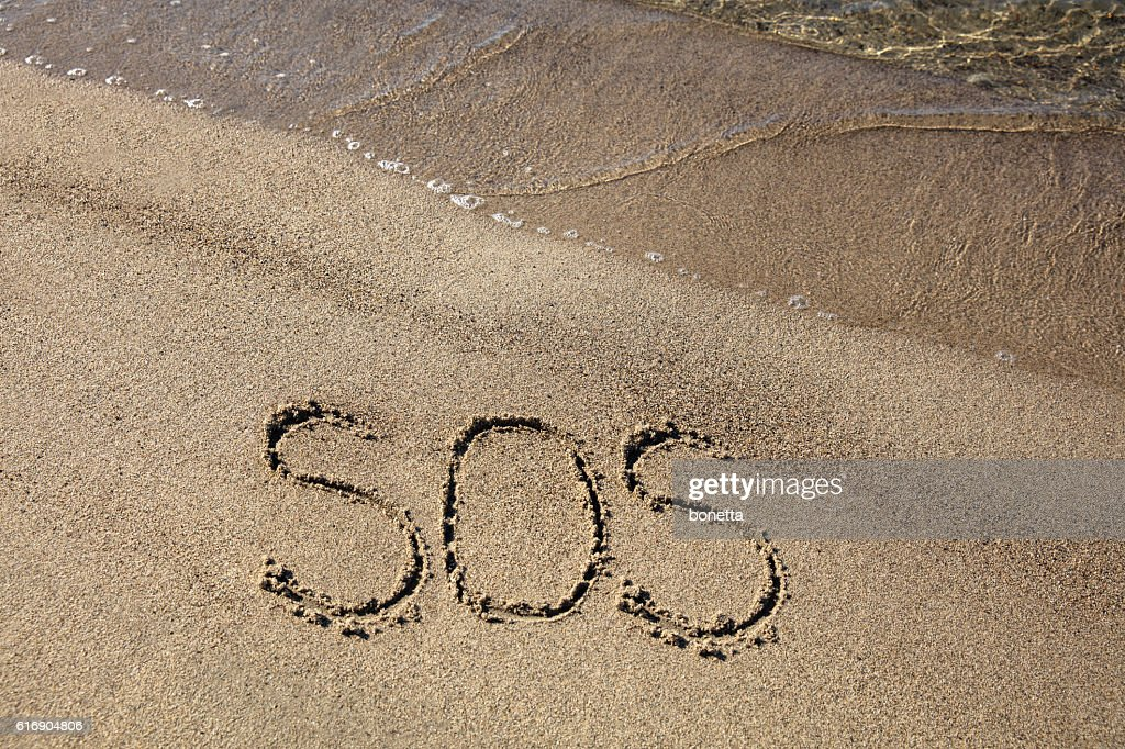 SOS sign on sandy beach : Stock Photo