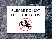 Black and white sign on stone wall with text PLEASE DO NOT FEED THE BIRDS and picture of bird and hand with food inside red crossed circle