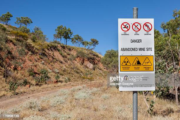 CONTENT] A sign on the road approaching an abandoned open cut uranium mine The sign warns of radiation hazard falling rocks unstable edges and the...