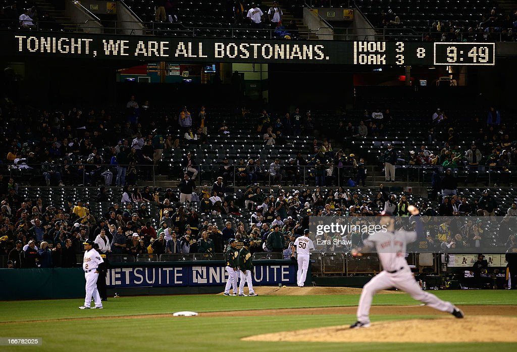 A sign on the scoreboard reads 'Tonight, we are all Bostonians' as Dallas Keuchel #60 of the Houston Astros warms up during the seventh inning of their game against the Oakland Athletics at O.co Coliseum on April 16, 2013 in Oakland, California.