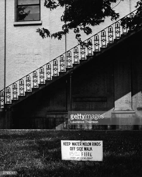 A sign outside a building in Richmond Kentucky reads 'Keep Watermelon Rinds Off Sidewalk $500 Fine' circa 1960