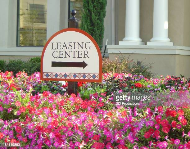 Sign Outside A Leasing Center Office Surrounded By Colorful Flowers