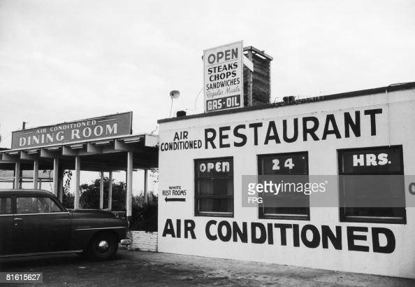 A sign outside an American restaurant points to the 'White Rest Rooms' in a clear indication of racial segregation circa 1960