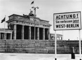 A sign outside the Brandenburg Gate and the Berlin Wall reading 'Attention You are now leaving West Berlin'