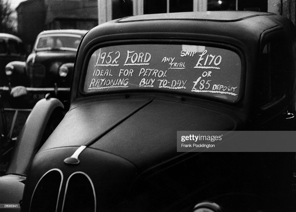A sign painted on the back window of a car stating: '1952 Ford. Ideal For Petrol Rationing. Buy Today - Any Trial ?170 or ?85 Deposit'. Original Publication: Picture Post - 9088 - Petrol Rationing - unpub.