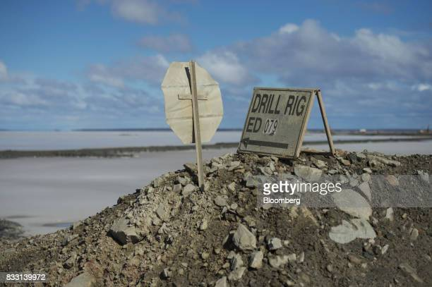 A sign pointing to a drill rig located on a salt lake sits at an access road of the St Ives Gold Mine operated by Gold Fields Ltd in Kambalda...