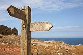 Sign post and tin mine ruins on coastal path, Trewellard, Penzance, Cornwall, UK