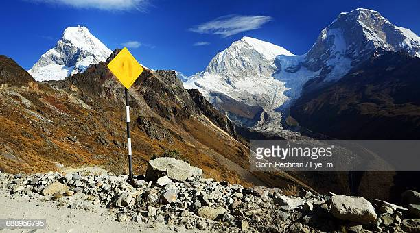 Sign Post By Stones With Mountain Peak In Background