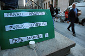 A sign questions the market system on Wall St across from the New York Stock Exchange October 2 2008 in New York City After passing in the Senate...