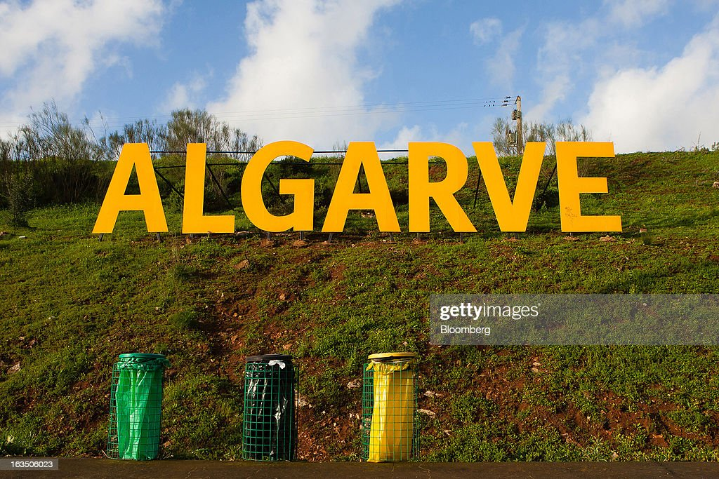 A sign reading 'Algarve' stands near an exit road on a highway embankment near color-coded recycling bins near Faro, Portgual, on Saturday, March 9, 2013. The tourism and real estate sector's recovery is crucial for Portugal's economy, which the government projects will return to growth next year, after shrinking an estimated 1 percent in 2013 and 3 percent in 2012. Photographer: Mario Proenca/Bloomberg via Getty Images
