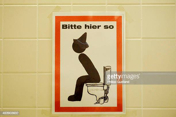 A sign reading 'Bitte hier so' and depicting a seated man with bavarian hat on a toilet is seen on a men's lavatory on the fairground four weeks...
