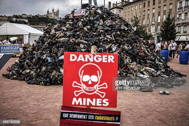 A sign reading ''Danger landmines what is happening to those shoes'' is pictured in front of a pyramid of shoes on September 20 2014 in Lyon central...