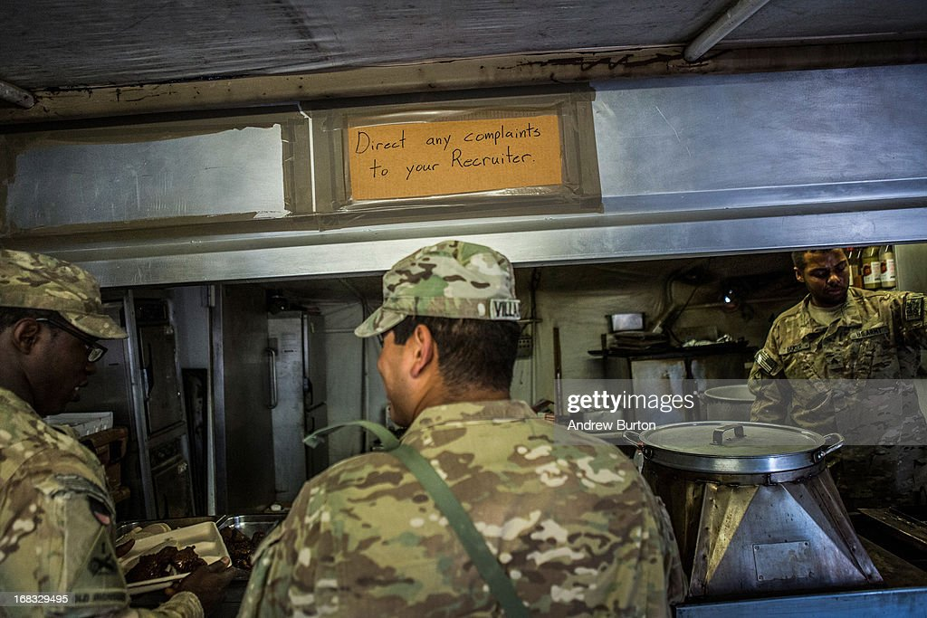 A sign reading, 'Direct any complaints to your recruiter' hangs above the stoves at the dining facility at Command Outpost Pa'in Kalay on March 20, 2013 in Kandahar Province, Maiwand District, Afghanistan. The United States military and its allies are in the midst of training and transitioning power to the Afghan National Security Forces in order to withdraw from the country by 2014.