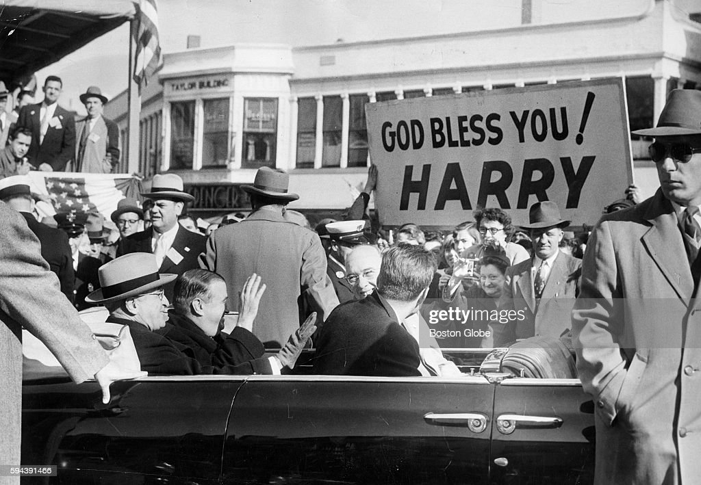 A sign reading 'God Bless You Harry' welcomes President Harry S Truman at Taunton Mass on Oct 18 1952 Governor of Mass Paul A Dever sits beside him