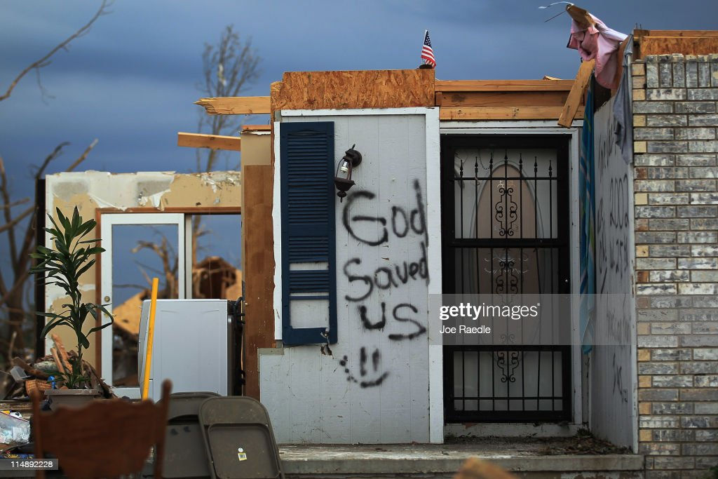 A sign reading, 'God Saved Us' is seen on the wall in front of a home that was damaged when a massive tornado passed through the town killing at least 125 people on May 27, 2011 in Joplin, Missouri. The town continues the process of recovering from the storm.